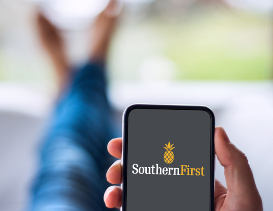 In focus, a hand holding a phone showing the Southern First loading screen and, out of focus, someone lounging with legs crossed.