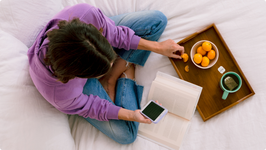 Top-down view of a person sitting cross-legged on a white comforter while browsing their phone and eating orange slices with a book open and a tray with a hot cup of tea in front of them.