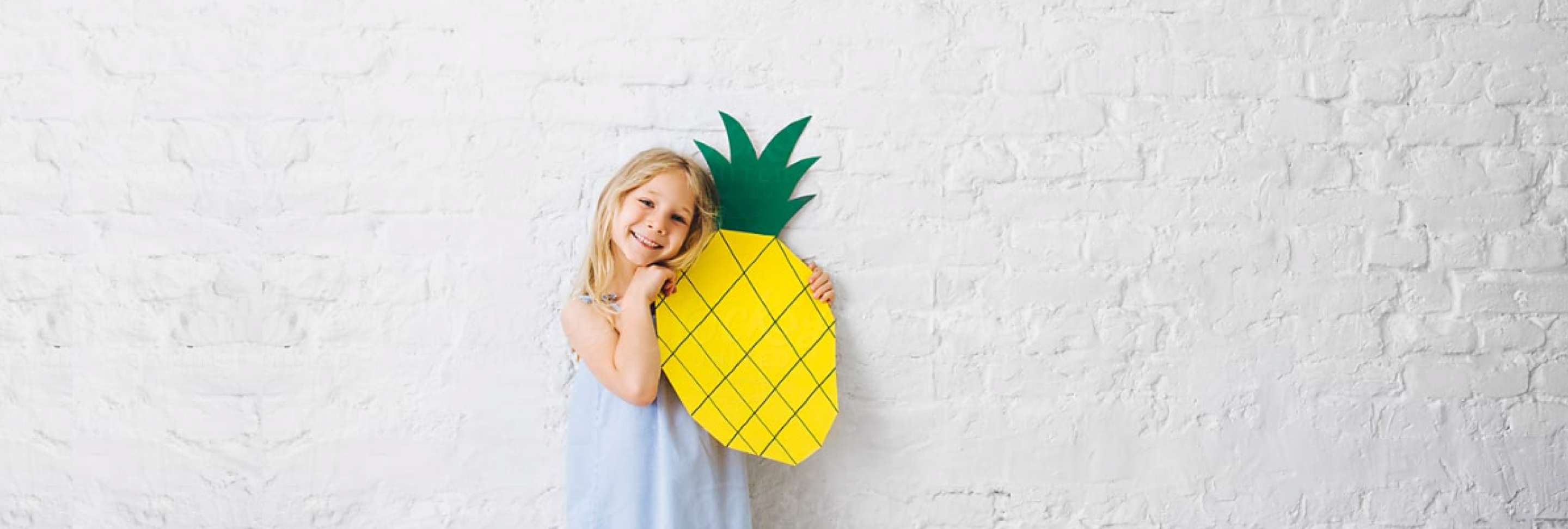 A little girl hugs a pineapple cardboard cut-out in front of a white brick wall