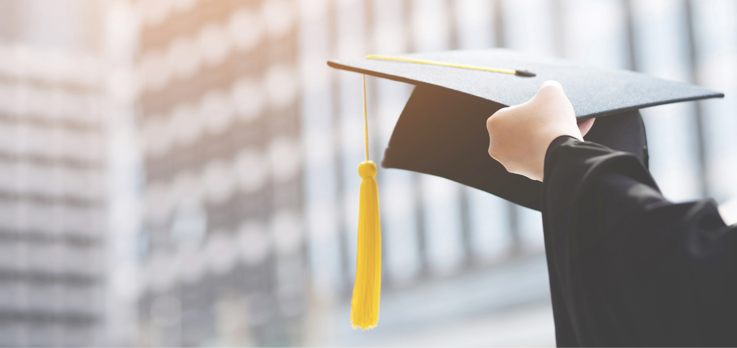 Hand holding graduation cap with tassel.