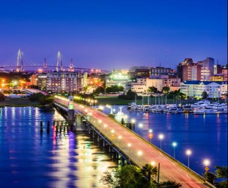 Charleston city view of bridge lit up at night.