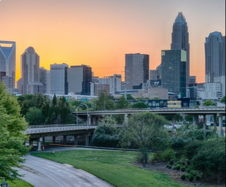 Skyline view of Charlotte from the highway at sunset.